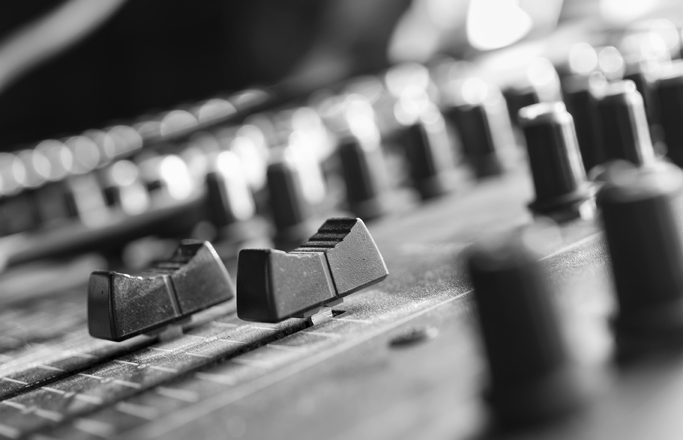 Macro shot of mixing console sliders, indoor horizontal composition with shallow depth of field